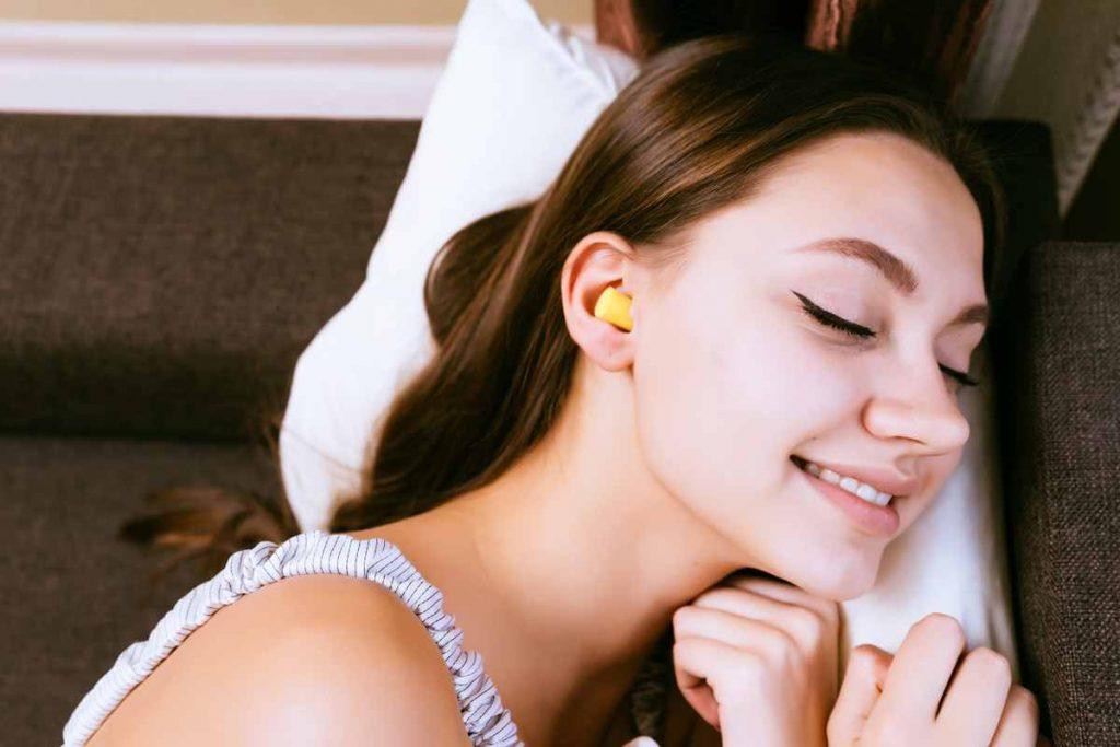 woman on side sleep earplugs